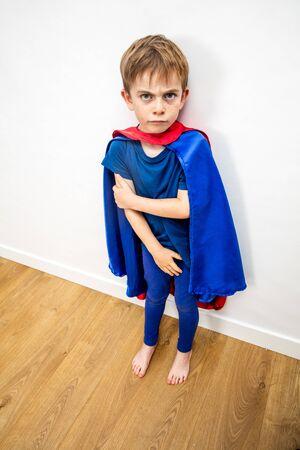 Niño pequeño superhéroe enojado en conflicto con sus padres por violencia doméstica, falta de respeto, castigo, decepción, vista de ángulo alta Foto de archivo
