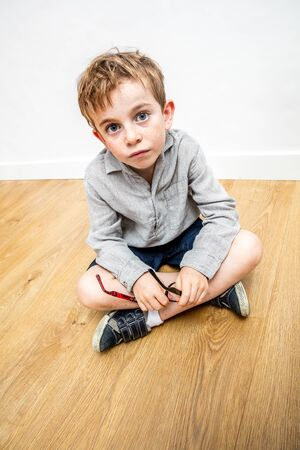 surprised beautiful little child thinking, holding his eyeglasses crossed legs expressing innocence and doubt about education with inferiority, high angle view