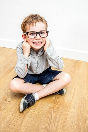 happy mischievous boy with nerd eyeglasses covering his ears not to hear, not listening for respect of himself, crossed legs on wooden floor Stock Photo