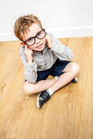 confident or stubborn boy body language and attitude, not listening, disagreeing, covering his ears to ignore to be looked down as a child, abusive high angle view