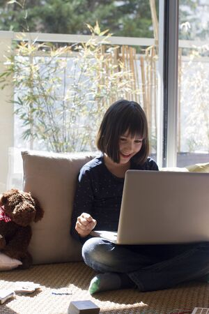 laughing child sitting with screen on lap, playing with teddy bear, enjoying homeschooling with computer to learn online, sunny balcony background