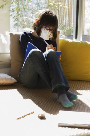 lockdown child with protection face mask writing on exercise notebook sitting while class closure, sunny green balcony background Imagens