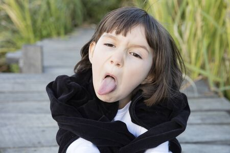 outdoor portrait of a goofy young child making a naughty grimace, sticking out his tongue for misbehavior and violent childhood, green environment background
