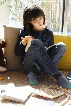 studious child reading a book home with teddy bear and board games around, learning and studying for homeschool while corona virus lockdown