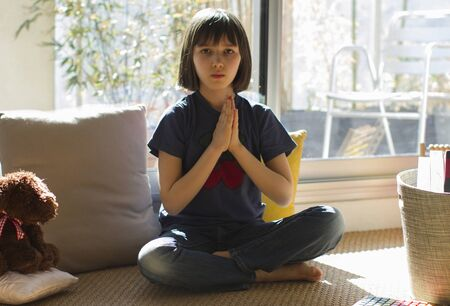 kid in lockdown enjoying namaste while practicing yoga with teddy bear for sunny quarantine at home, bamboo balcony background