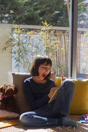 cheerful child laughing, expressing surprise, finding solution while playing on board games in covid-19 lockdown with teddy bear in sunny apartment with green balcony Stock Photo