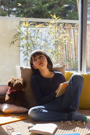 desperate child crying, feeling lonely and bored while playing and studying for homeschooling in covid-19 lockdown and school shutdown in sunny apartment Stock Photo