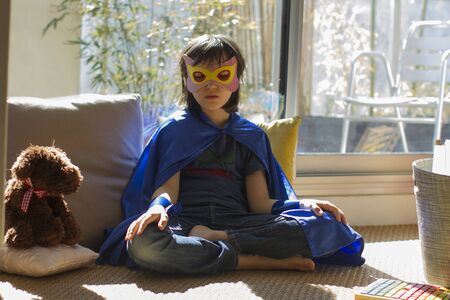 serious superhero lockdown child dressed up with mask and teddy bear seeking for inner peace from yoga, meditation and mindfulness to relax facing virus shutdown