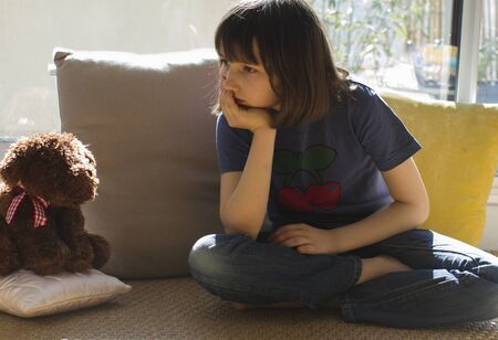 thoughtful child daydreaming, bored or depressed of studying alone with teddy bear for homeschooling in corona virus lockdown and school shutdown Stock Photo