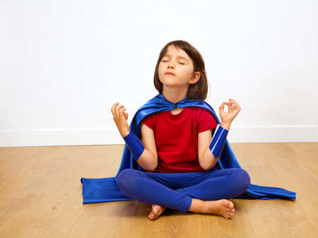 calm superhero child practicing fun yoga with feet and closed eyes for meditating at home seated on wooden floor, white background
