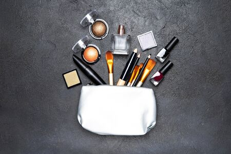 Decorative cosmetics and cosmetic bag on a black background