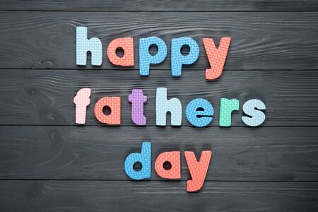 Text happy dad's day on a gray wooden background