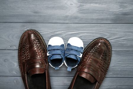 Happy father's day concept. Shoes of dad and little son on a wooden background. Place for text