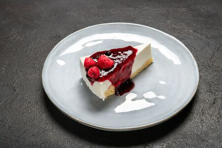 Plate with a piece of cheesecake with jam and raspberries Imagens