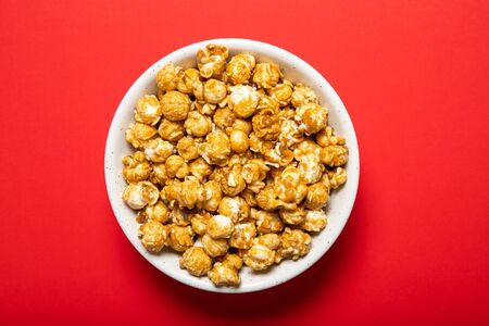 Plate with caramel popcorn on a red background Stok Fotoğraf - 147588133