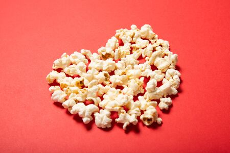 Delicious popcorn on a red background. Top view, place for text.