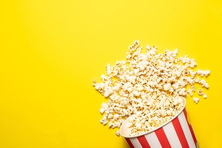 Paper cup with popcorn on a yellow background, place for text.