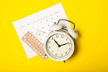 Female birth control pills, calendar and alarm clock on a yellow background. Close-up