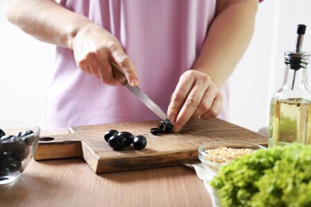 Woman cuts black olives. The process of making salad