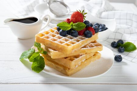 Delicious Belgian waffles with strawberries, blueberries and mint on a plate