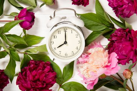 Peonies and alarm clock on a wooden background.