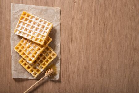 Delicious Belgian waffles with honey. Bakery products. View from above