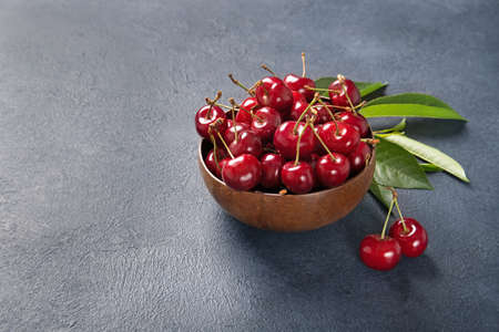 Plate with fresh cherries with green leaves. Black background. Place for text