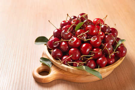Wooden plate with sweet cherries on the table