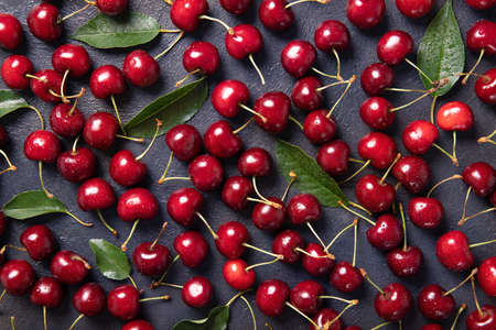 Sweet cherry on a black background with leaves and drops of water. View from above