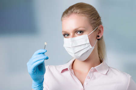 dentist's assistant / female dentist with dental face mask holds / shows hade guide to check veneer of tooth Banco de Imagens