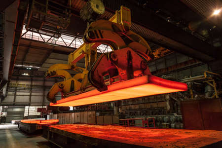 A slap in a steel mill is lifted from a freight car