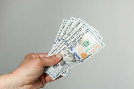 man's hand with a bunch of hundred dollar bills in front of a gray background Stock Photo