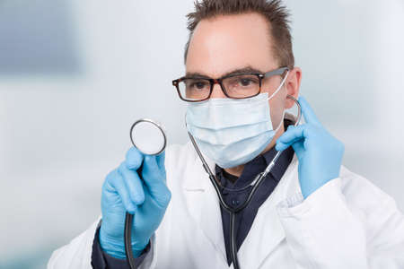 male family doctor with face mask and stethoscope in front of a clinic room Banco de Imagens