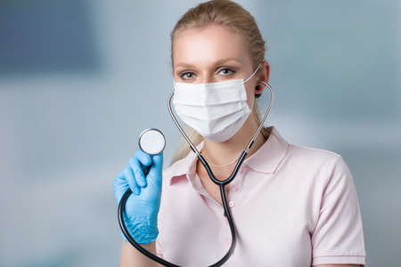 young female family doctor with face mask and stethoscope in front of a clinic room Banco de Imagens
