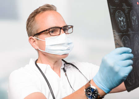 male doctor with medical face mask in front of a clinic room looks at an x-ray scan Banco de Imagens