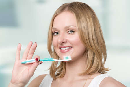 Young smiling blonde woman shows her white teeth and her tooth brush Stok Fotoğraf