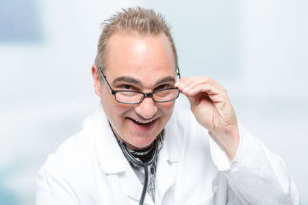 happy male doctor in front of a clinic room Banco de Imagens