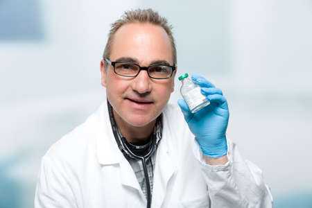 happy male doctor in front of a clinic room presenting a vaccine bottle