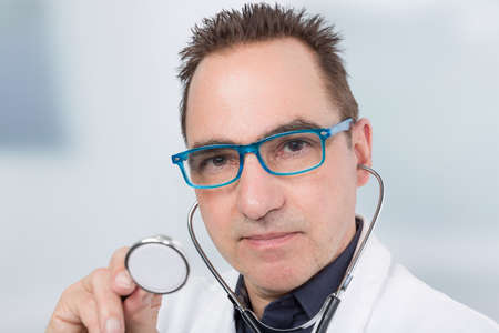 male doctor in front of a clinic room is handling a stethoscope Banco de Imagens