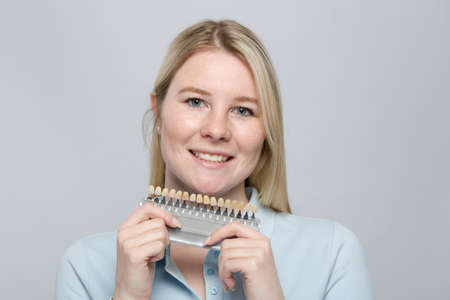 young woman presenting a dentist's shade guide to check veneer of teeth for bleaching