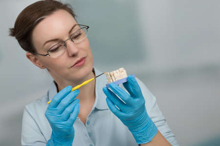 female dental technician doing painting work on denture parts in a dental laboratory