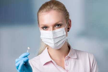 dentist's assistant or female dentist with dental face mask shows shade guide to check veneer of tooth in front of a dentistry room 版權商用圖片