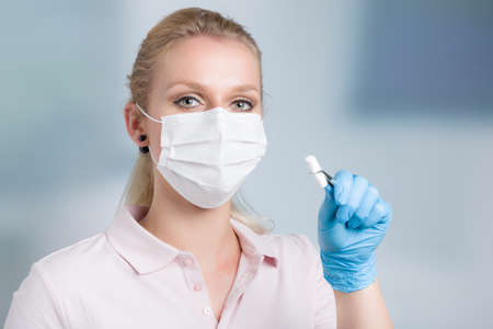 dentist's assistant or female dentist with dental face mask shows cotton roll in front of a dentistry room 版權商用圖片