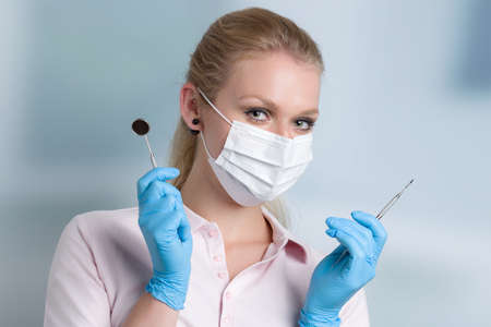 dentist's assistant or female dentist with dental face mask shows dental instruments in front of a dentistry room