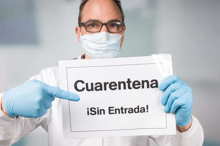 Doctor with medical face mask and medical gloves pointing to spanish quarantine sign in front of a restricted area