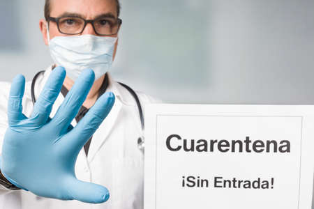 Doctor with medical face mask and medical gloves showing spanish quarantine sign and makes a stop gesture in front of a restricted area 版權商用圖片