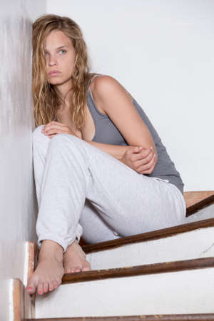Lonely young woman in casual clothes sitting on stairs looking sadly 版權商用圖片