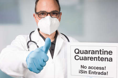 Doctor with medical face mask and medical gloves showing spanish written quarantine sign in front of a restricted area and shows thumbs up 版權商用圖片