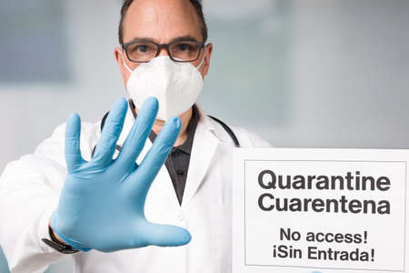 Doctor with medical face mask and medical gloves showing spanish written quarantine sign in front of a restricted area