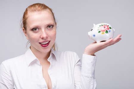 Young happy red-haired woman holding a piggy bank / porcelain bank in her hand